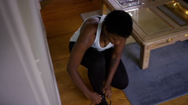 Young woman ties shoes before going on a run.