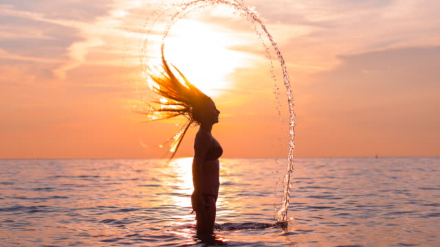 Young woman tossing hair in water at sunset