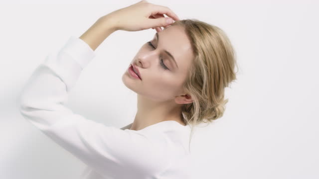Young woman touching her face against wall