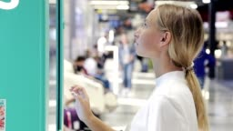Young woman touching sensitive screen in shopping Mall