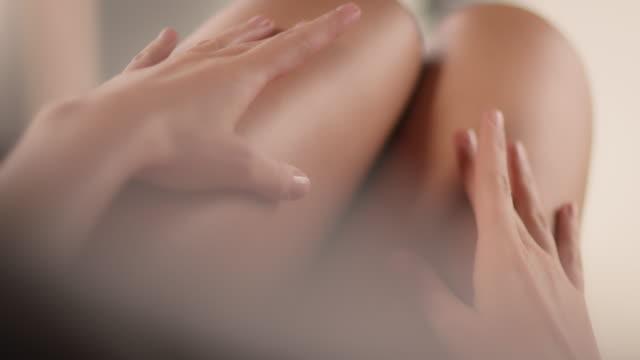 giovane donna che tocca gambe eleganti lisce - coscia gamba umana video stock e b–roll