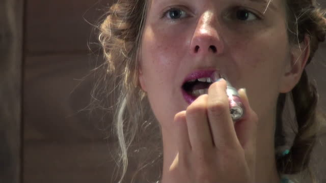 young woman touching up her lips with intense pink lipstick - pink lipstick stock videos and b-roll footage