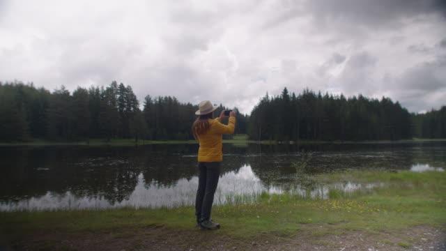 vídeos de stock e filmes b-roll de young woman tourist taking photos near a mountain lake. wanderlust. - eco tourism