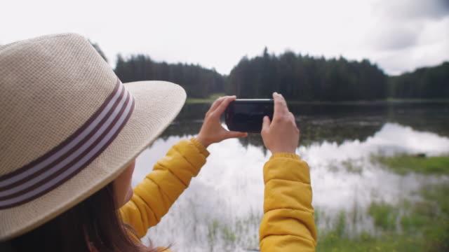 young woman tourist taking photos near a mountain lake. wanderlust. - eco tourism stock videos & royalty-free footage