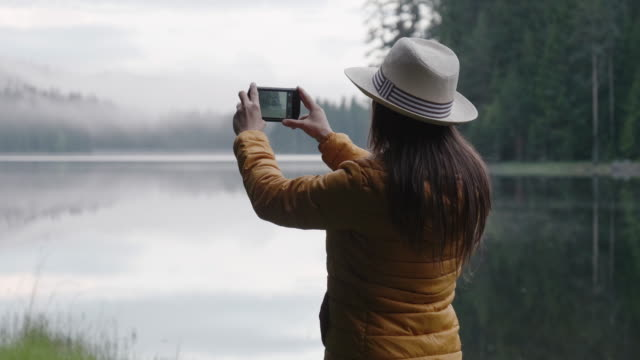 young woman tourist taking photos near a mountain lake. wanderlust. - eco tourism stock videos & royalty-free footage
