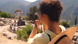 Young woman tourist taking pictures at temple of Athena Pronaia in archaeological site of Delphi, Voiotia, Greece. Fashion elegant yellow dress, large hat, vintage camera.
