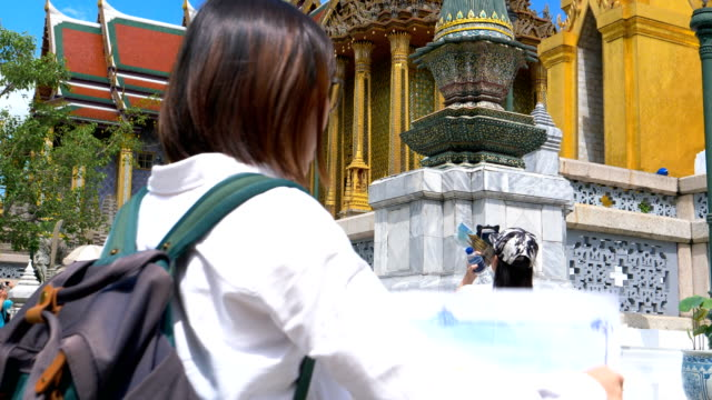 young woman tourist traveling in grand palace at bangkok thailand on summer holidays - palacio stock videos & royalty-free footage