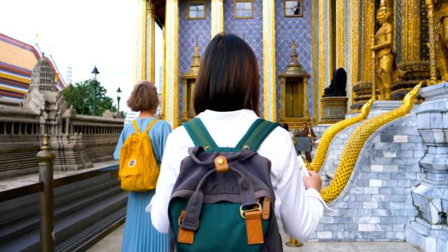 stockvideo's en b-roll-footage met jonge vrouw toeristische reizen in grand palace in bangkok thailand - tempel