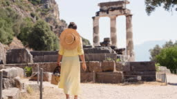 Young woman tourist visiting temple of Athena Pronaia in archaeological site of Delphi, Voiotia, Greece. Fashion elegant yellow dress, large hat.