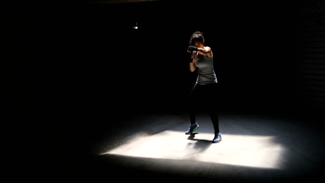 young woman training and a punching imaginary bag - kickboxing stock videos & royalty-free footage