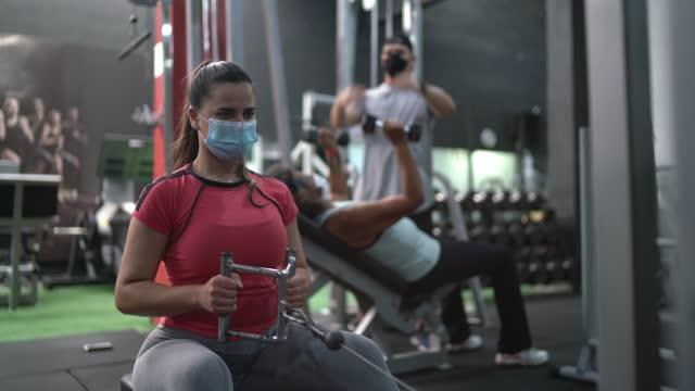 giovane donna che si allena in palestra - usando la maschera facciale - irriducibilità video stock e b–roll