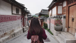 Young woman traveler take a photo by smartphone and traveling into Bukchon Hanok Village at Seoul city, South Korea