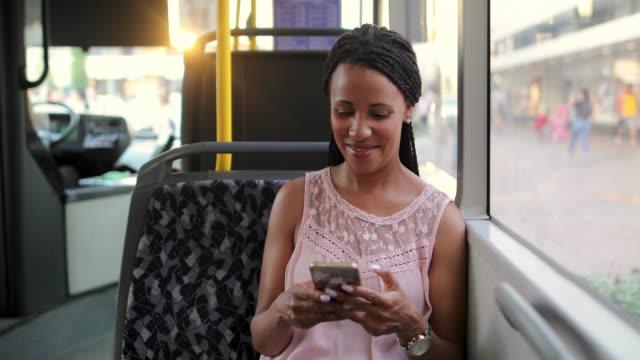 vidéos et rushes de jeune femme voyageant par un autobus et utilisant le téléphone intelligent - transports publics
