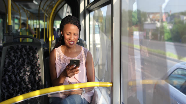 young woman traveling by a bus and using smart phone - public transportation stock videos & royalty-free footage