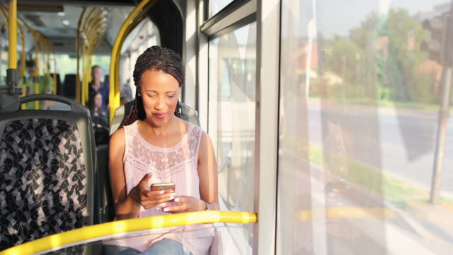 young woman traveling by a bus and using smart phone - autobus video stock e b–roll