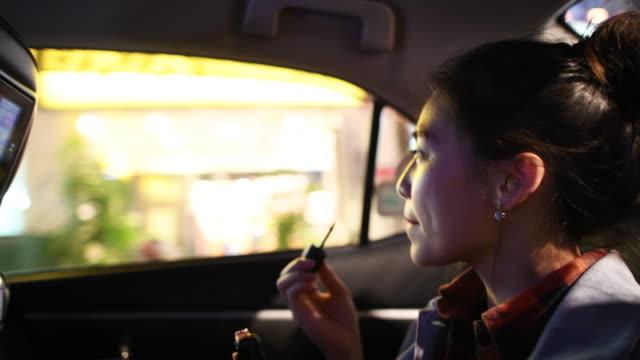 口紅をつけてタクシーの後ろを旅する若い女性 - タクシー点の映像素材/bロール