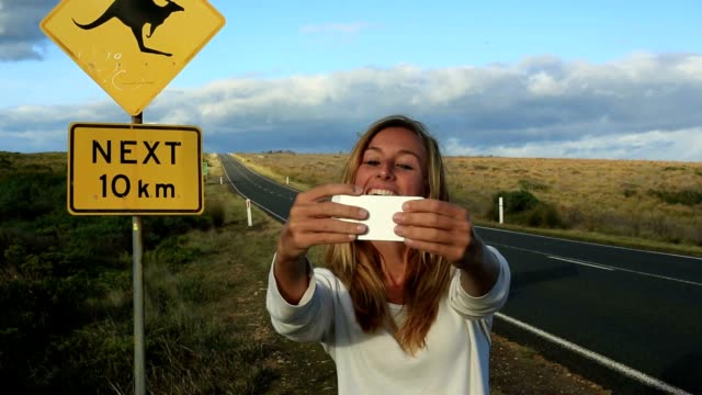 young woman traveling takes selfie with kangaroo crossing sign - road warning sign stock videos & royalty-free footage