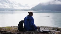 A young woman traveller sitting by the Norwegian fjord