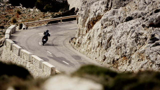 young woman travelling on a motorcycle. rocky coastline - helmet motorcycle stock videos and b-roll footage