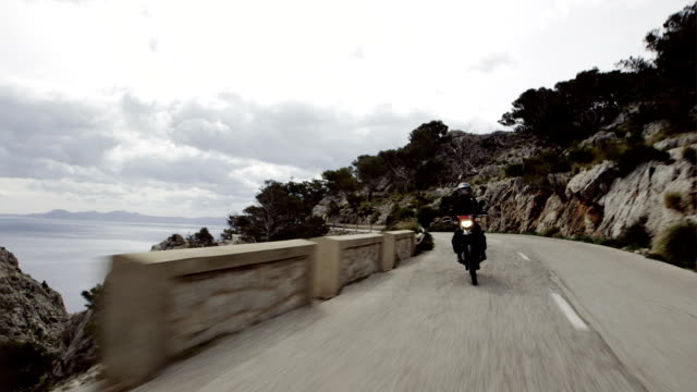 Young woman travelling on a motorcycle. Rocky coastline