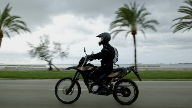 Young woman travelling on a motorcycle. Tropical climate
