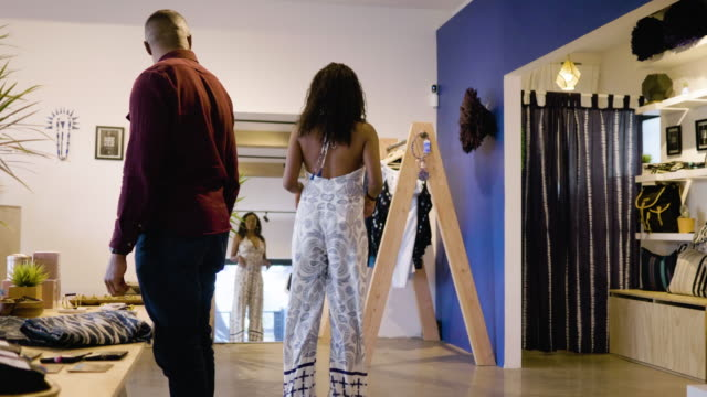a young woman tries on an african jumpsuit and looks at herself in a mirror in a clothing boutique, as her husband looks on approvingly - jumpsuit stock videos and b-roll footage