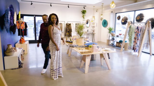 a young woman tries on an african jumpsuit and looks at herself in a mirror in a clothing boutique, as her husband looks on approvingly - husband stock videos & royalty-free footage