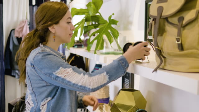 vídeos de stock, filmes e b-roll de a young woman tries on bracelets in a clothing boutique - jaqueta jeans