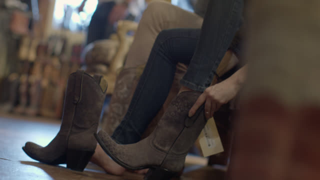 young woman tries on cowboy boots with friend and dances around western store - leather shoe stock videos and b-roll footage