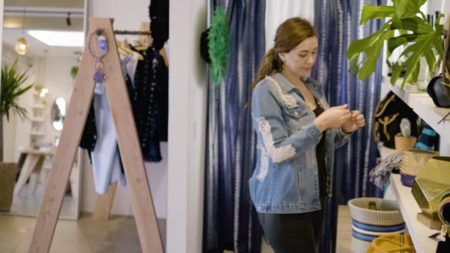 a young woman tries on sunglasses in a clothing boutique - anpassen stock-videos und b-roll-filmmaterial