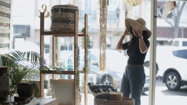 young woman trying on a hat in a store - hat stock videos & royalty-free footage
