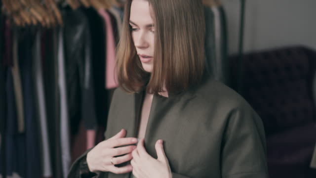 young woman trying on coat in clothing store - vestirsi video stock e b–roll