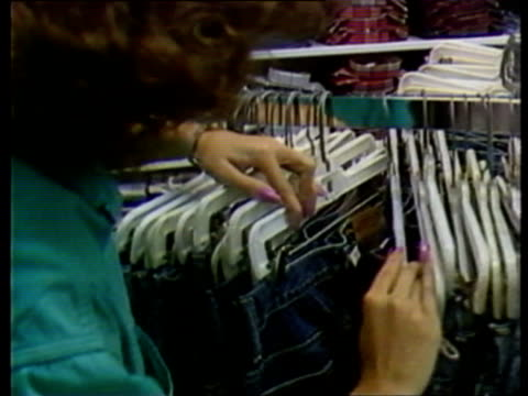 vídeos de stock e filmes b-roll de young woman trying on levi strauss jeans in store dressing room; woman sifting through jeans hanging on clothing rack; salesperson helping young... - jeans
