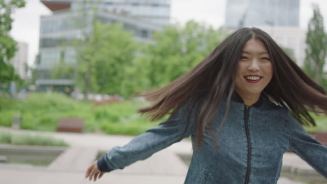 Young woman turning and smilling next to skyscraper