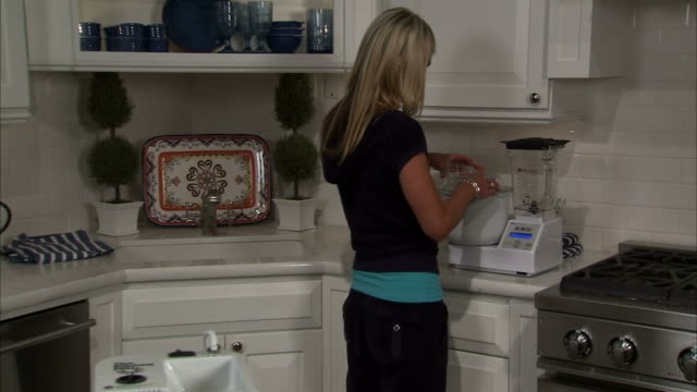 zi ms young woman turning on mixer in kitchen / salt lake city, utah, usa - korta ärmar bildbanksvideor och videomaterial från bakom kulisserna