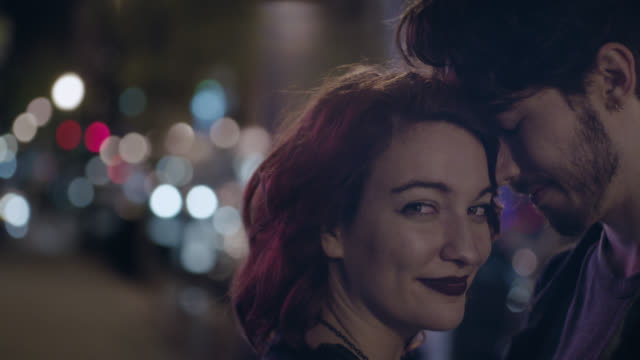 cu slo mo. young woman turns and smiles at camera as boyfriend holds her close on city street corner. - ansikte mot ansikte bildbanksvideor och videomaterial från bakom kulisserna