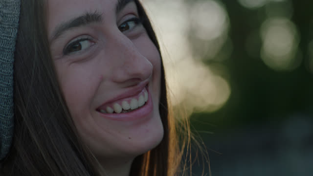 CU SLO MO. Young woman turns to look at camera and laughs.