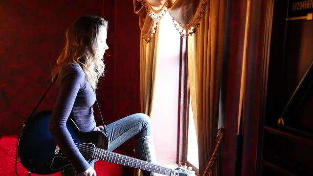 vidéos et rushes de hd : jeune femme à la fenêtre, se joue de la guitare - guitare électrique