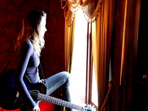 Junge Frau macht Fenster, spielt Gitarre