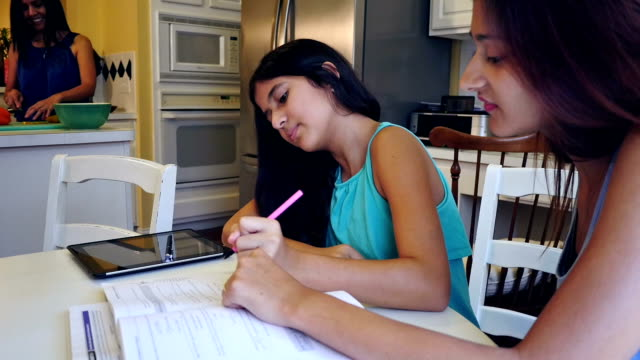 young woman tutoring her preteen sister at home in family kitchen - homework stock videos & royalty-free footage