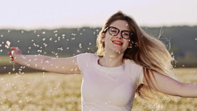 SLO MO jonge vrouw twirling onder paardebloem zaden