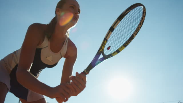 young woman twirling tennis racket in slow motion against bright blue sky - anticipation点の映像素材/bロール