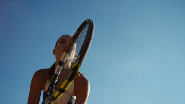 vídeos de stock e filmes b-roll de young woman twirling tennis racket in slow motion against bright blue sky - raqueta