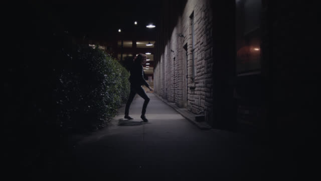 ws slo mo. young woman twirls around gracefully dancing under streetlights in urban alleyway at night. - rebellion video stock e b–roll