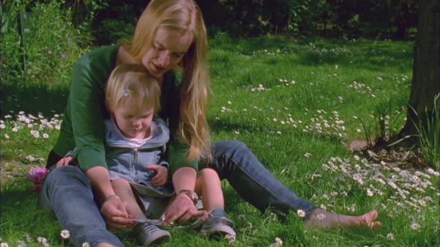 vidéos et rushes de ms, young woman tying daughter's (2-3) shoelaces in garden, brussels, belgium - nouer