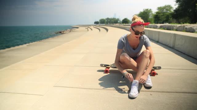 vídeos y material grabado en eventos de stock de a young woman tying her shoes while sitting on her longboard skateboard. - patinaje en tabla larga