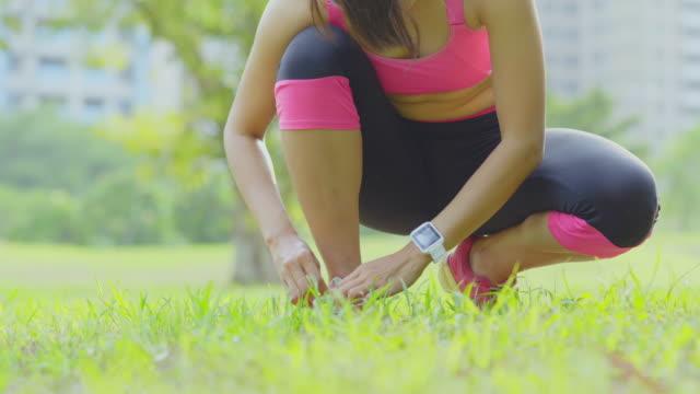 vidéos et rushes de jeune femme attacher le lacet sur sentier forestier - joggeuse