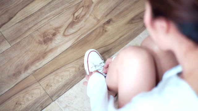 young woman tying shoelaces on floor. - calzature video stock e b–roll