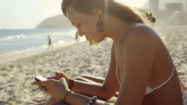 ms a young woman types on her smartphone on ipanema beach / rio de janeiro, brazil - text messaging stock videos & royalty-free footage