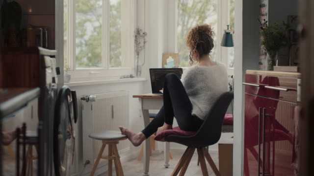 young woman typing on laptop at home in berlin - leggings stock videos & royalty-free footage